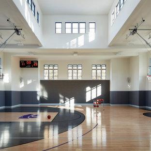 Esempio di un ampio campo sportivo coperto classico con pareti bianche, pavimento in legno massello medio e pavimento grigio