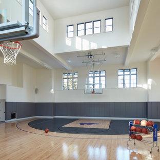 Immagine di un ampio campo sportivo coperto chic con pareti bianche, pavimento in legno massello medio e pavimento grigio