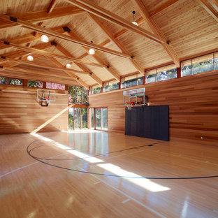 Großer Moderner Fitnessraum mit Indoor-Sportplatz, brauner Wandfarbe, hellem Holzboden und braunem Boden in Boston
