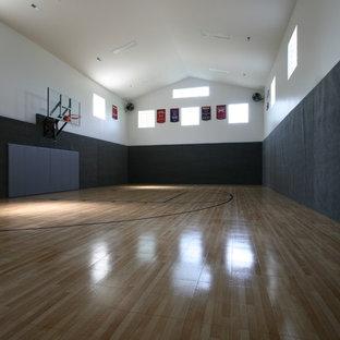 Ispirazione per un grande campo sportivo coperto tradizionale con pareti nere e parquet chiaro