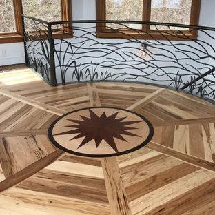 Mittelgroßer Uriger Yogaraum mit weißer Wandfarbe, hellem Holzboden, braunem Boden und freigelegten Dachbalken in Charlotte