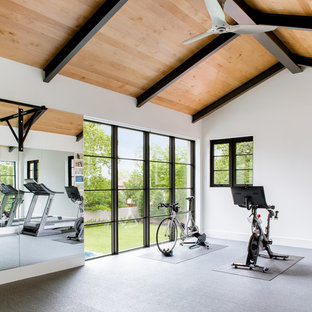 This is an example of a large mediterranean home gym in Dallas with white walls and grey floor.