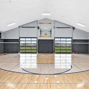 Ispirazione per un ampio campo sportivo coperto country con pareti grigie e parquet chiaro