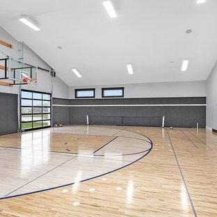 Idee per un ampio campo sportivo coperto country con pareti grigie, parquet chiaro e pavimento marrone