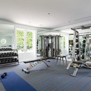 Immagine di una grande sala pesi design con pareti bianche, moquette e pavimento multicolore