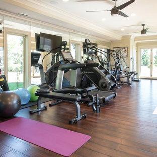Foto di una sala pesi tradizionale di medie dimensioni con pareti beige e pavimento in legno massello medio