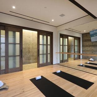 Immagine di uno studio yoga contemporaneo di medie dimensioni con pareti grigie, parquet chiaro e pavimento marrone
