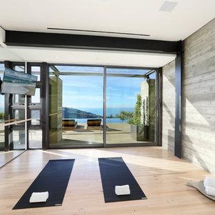 Ispirazione per uno studio yoga contemporaneo di medie dimensioni con pareti grigie, parquet chiaro e pavimento marrone