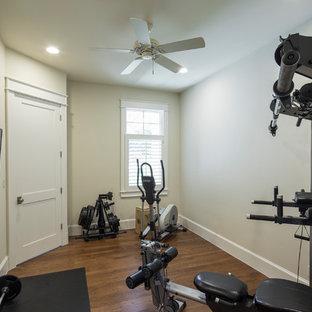 Esempio di una sala pesi stile americano di medie dimensioni con pareti grigie e pavimento in legno massello medio