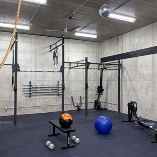 Diseño de sala de pesas urbana con paredes grises y suelo azul