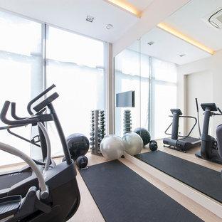 Multifunktionaler, Kleiner Moderner Fitnessraum mit hellem Holzboden in Surrey