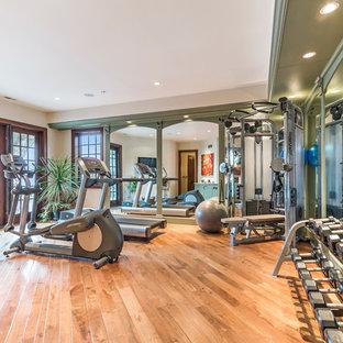 Idee per una grande sala pesi contemporanea con pareti beige e pavimento in legno massello medio