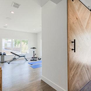 Inspiration pour un grand studio de yoga design avec un mur blanc et un sol en bois clair.