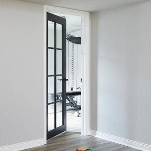 Foto di una piccola sala pesi minimal con pareti beige, pavimento in laminato e pavimento grigio