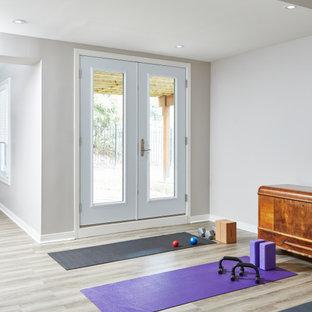 Ispirazione per uno studio yoga contemporaneo di medie dimensioni con pareti bianche, pavimento in laminato e pavimento grigio