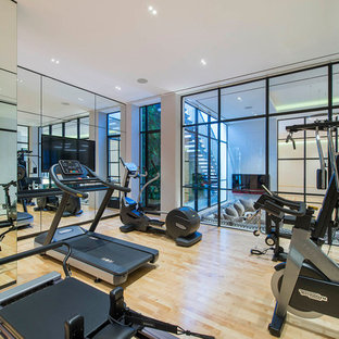 Design ideas for a large traditional home gym in London with beige floors and light hardwood flooring.