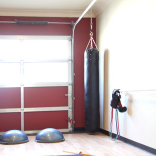 Kleiner Moderner Yogaraum mit roter Wandfarbe und hellem Holzboden in Calgary