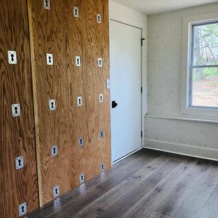 Esempio di uno studio yoga american style con pareti bianche, pavimento in laminato e pavimento marrone