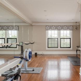 Ispirazione per una sala pesi costiera di medie dimensioni con pareti beige e pavimento in legno massello medio