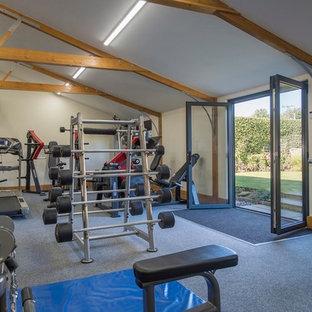Exemple d'une grand salle de musculation nature avec un mur beige, moquette et un sol gris.