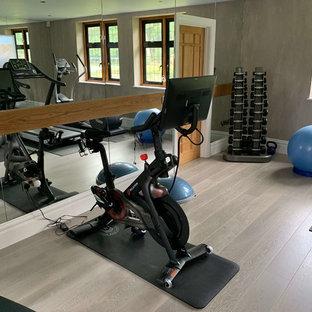 Ispirazione per una sala pesi design di medie dimensioni con pareti grigie, pavimento in legno verniciato e pavimento beige