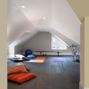 Immagine di uno studio yoga tradizionale di medie dimensioni con pareti grigie, parquet scuro e pavimento marrone