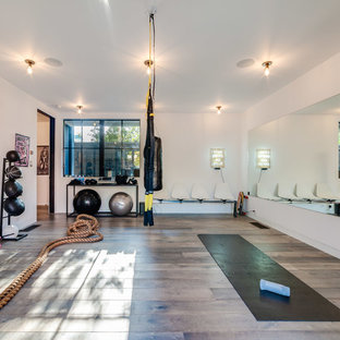 Design ideas for a mid-sized contemporary multipurpose gym in Los Angeles with white walls, grey floor and medium hardwood floors.