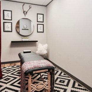 Idee per una grande palestra multiuso design con pareti grigie, pavimento in laminato e pavimento marrone