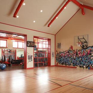 Geräumiger Industrial Fitnessraum mit Indoor-Sportplatz, weißer Wandfarbe und hellem Holzboden in Minneapolis