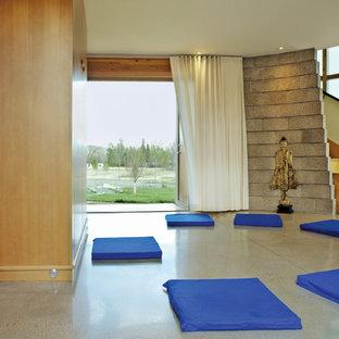 Idee per uno studio yoga design con pareti beige e pavimento in cemento