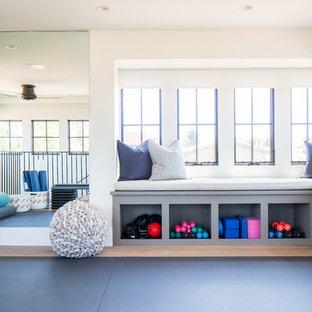 Ispirazione per un grande studio yoga mediterraneo con pareti bianche, pavimento in legno massello medio e pavimento marrone
