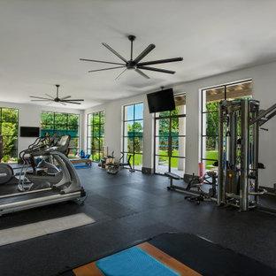 Multifunktionaler Mediterraner Fitnessraum mit weißer Wandfarbe und schwarzem Boden in Dallas