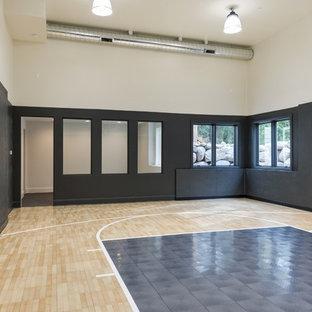 Großer Moderner Fitnessraum mit beigem Boden, Indoor-Sportplatz, schwarzer Wandfarbe und hellem Holzboden in Minneapolis