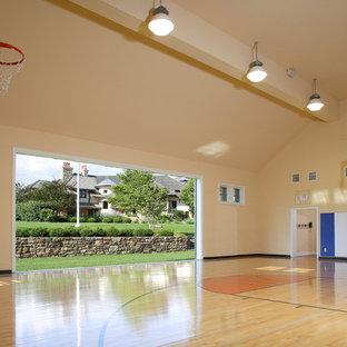 Immagine di un grande campo sportivo coperto tradizionale con pareti gialle, parquet chiaro e pavimento beige