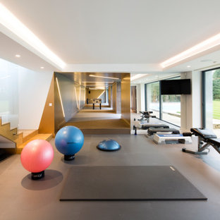Design ideas for an expansive contemporary multi-use home gym in London with grey floors.