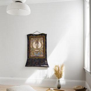 Cette image montre un studio de yoga nordique de taille moyenne avec un mur gris, un sol en bois clair et un sol marron.