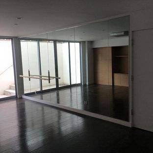 Idee per una grande palestra multiuso moderna con pareti bianche, parquet scuro e pavimento marrone