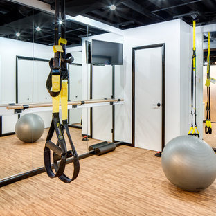 This is an example of a small industrial multi-use home gym in Columbus with white walls and cork flooring.