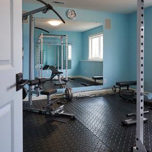 Foto di una sala pesi classica di medie dimensioni con pareti blu e pavimento nero