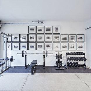 Foto di una palestra in casa moderna con pareti bianche, pavimento in cemento e pavimento grigio