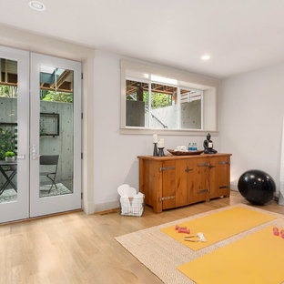 Esempio di uno studio yoga moderno di medie dimensioni con pareti grigie e parquet chiaro