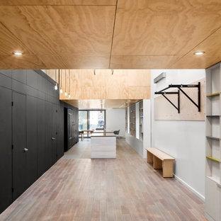 Ispirazione per una grande sala pesi minimal con pareti bianche, pavimento in legno massello medio e pavimento multicolore