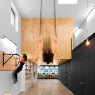 Idee per una grande sala pesi contemporanea con pareti bianche, pavimento in legno massello medio e pavimento multicolore