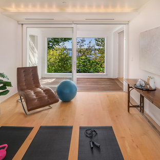 Design ideas for a beach style home yoga studio in Seattle with white walls, medium hardwood floors and brown floor.