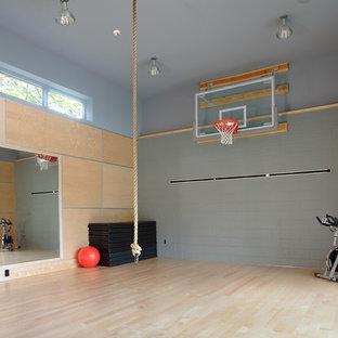 Modelo de pista deportiva cubierta moderna, grande, con paredes grises y suelo de madera clara