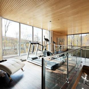 Moderner Fitnessraum mit beiger Wandfarbe, dunklem Holzboden und braunem Boden in Montreal