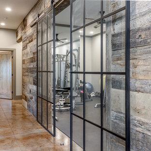 Foto di una sala pesi stile rurale di medie dimensioni con pareti beige, pavimento in cemento e pavimento marrone