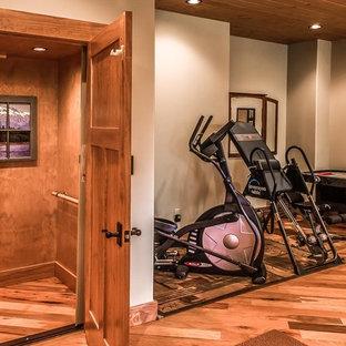 Immagine di una grande palestra multiuso american style con pareti bianche, pavimento in legno massello medio e pavimento marrone
