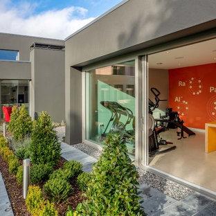 Foto di una sala pesi design con pareti arancioni e pavimento beige