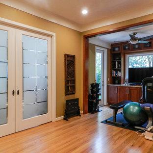 Ispirazione per una sala pesi classica con pareti gialle e parquet chiaro